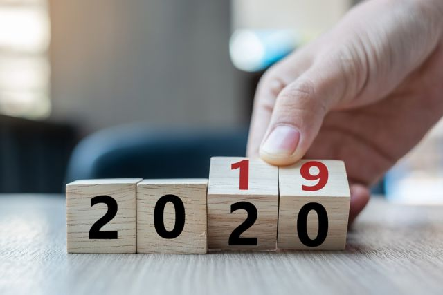 Business man hand holding wooden cube with flip over block 2019 to 2020 word on table background. Resolution, strategy, solution, goal, business, New Year New You and happy holiday concepts