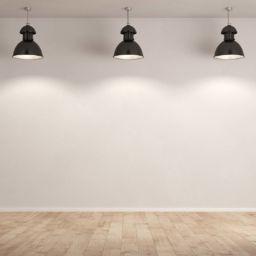 Drei Lampen hängen im Raum vor einer weißen Wand