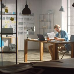 Professional Creative Designer Works on a Laptop in Loft Office, Looks at the Product Sketches and Concepts He Has Drawn. Stylish Design or Gaming Content Development Studio. Golden Hour Shot