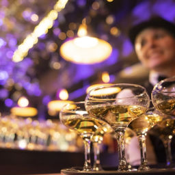 happy waitress holding a tray full of glasses or welcome drinks at an event